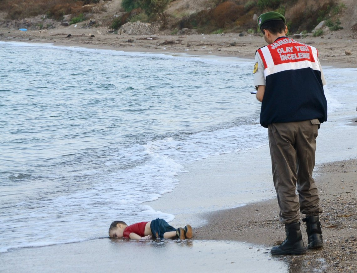 A Turkish gendarmerie stands next to a young migrant, who drowned in a failed attempt to sail to the Greek island of Kos, as he lies on the shore in the coastal town of Bodrum, Turkey